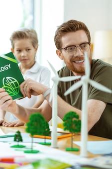 Jonge leerlingen. tevreden gemberleraar met heldere bril die tijd doorbrengt met kleine jongens tijdens cognitieve lessen
