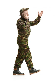 Jonge legermilitair die geïsoleerde camouflage eenvormig draagt
