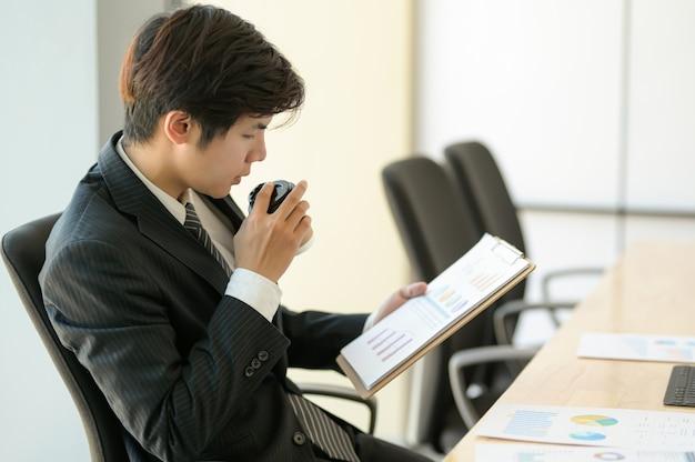 Jonge leidinggevenden controleren de bedrijfsresultaten. hij eet koffie en controleert de kaart.