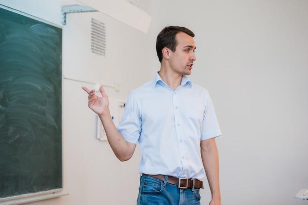 Jonge leraar dichtbij bord in schoolklaslokaal dat aan klasse spreekt