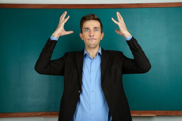 Jonge leraar dichtbij schoolbord in schoolklas