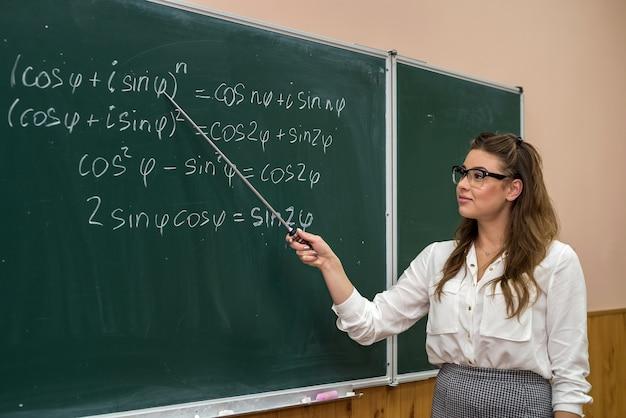 Jonge leraar die de wiskundige formules op een schoolbord schrijft en uitlegt. opleiding