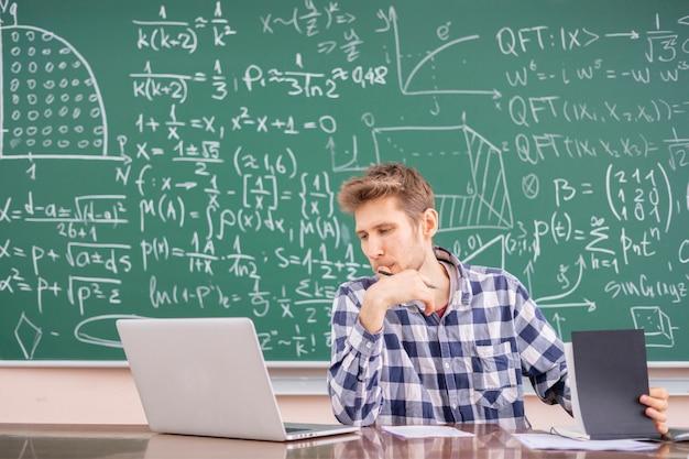 Jonge leraar die met laptop werkt of een online collegewebinar geeft