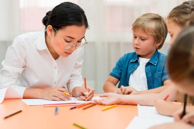 Jonge leraar doet haar klas met kinderen
