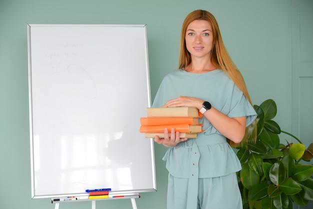 Jonge leraar geeft les in de buurt van het bord met boeken