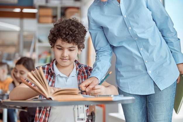 Jonge leraar helpt haar student te lezen. basisschoolkinderen zittend op een bureau en het lezen van boeken in de klas.