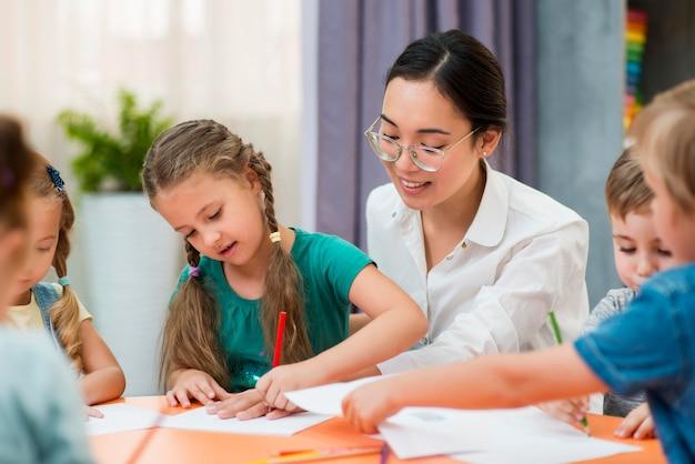 Jonge leraar helpt haar studenten in de klas