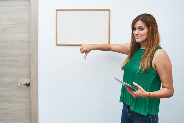 Jonge leraar lesgeven met een wit bord en een tablet.