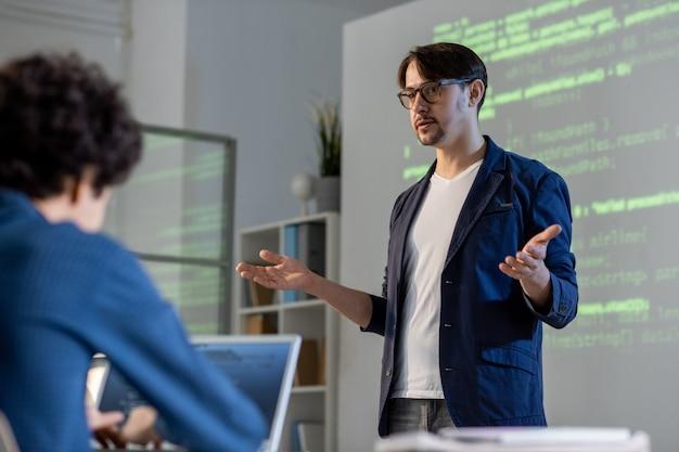 Jonge leraar of coach in vrijetijdskleding en bril die enkele moeilijke punten aan studenten uitlegt of hun vragen beantwoordt tijdens een seminarie