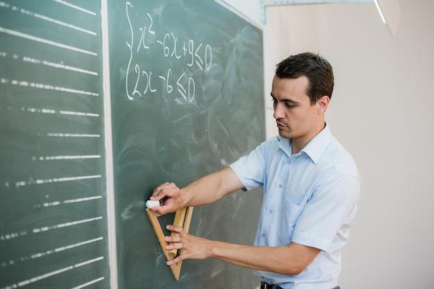 Jonge leraar of student tekenen driehoek op een bord met formule