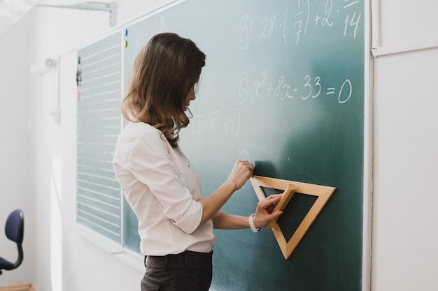Jonge leraar of student tekenen driehoek op een schoolbord met formule