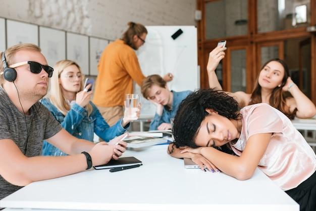 Jonge leraar schrijft aan boord terwijl studenten aan tafel zitten en niet naar hem luisteren tijdens de les