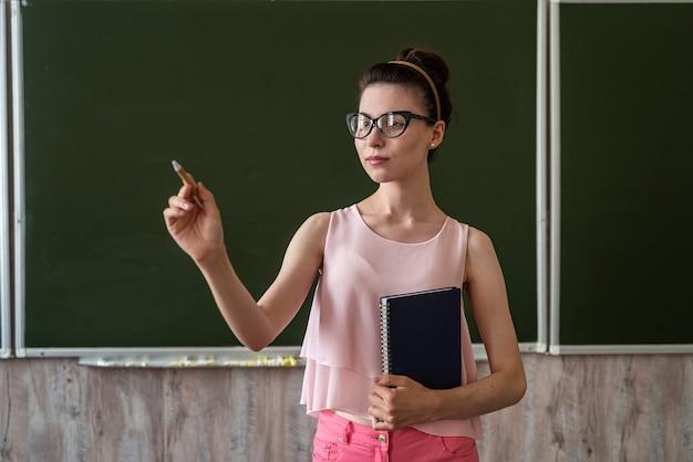 Jonge leraar staat in de buurt van leeg bord en legt nieuwe les uit