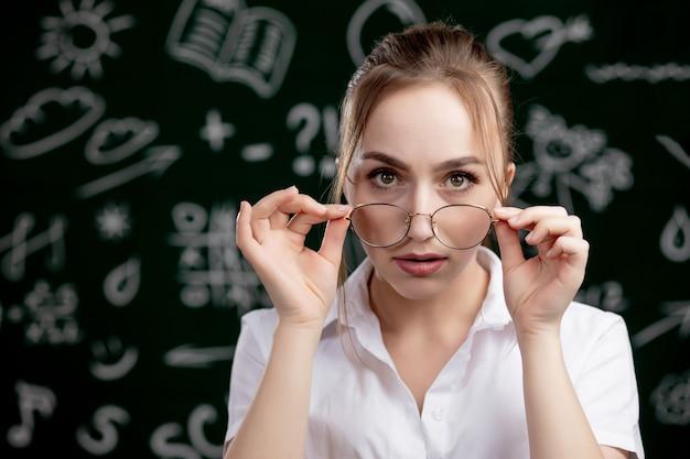 Jonge leraar staat in de buurt van schoolbord in de klas