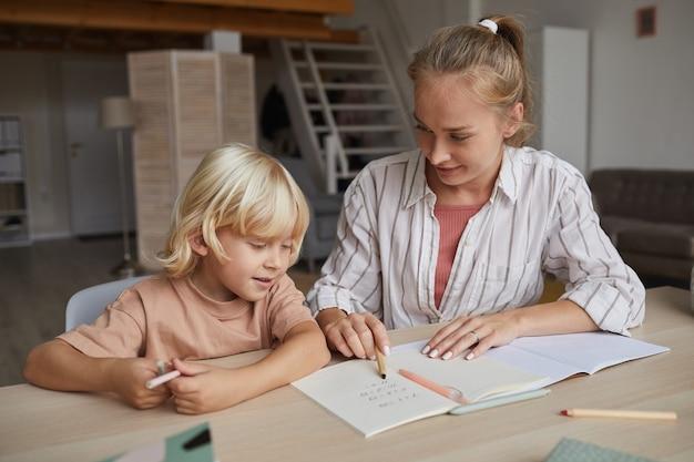 Jonge leraar wijzend op notitie boek en het kind onderwijzen aan een nieuw onderwerp aan de tafel thuis