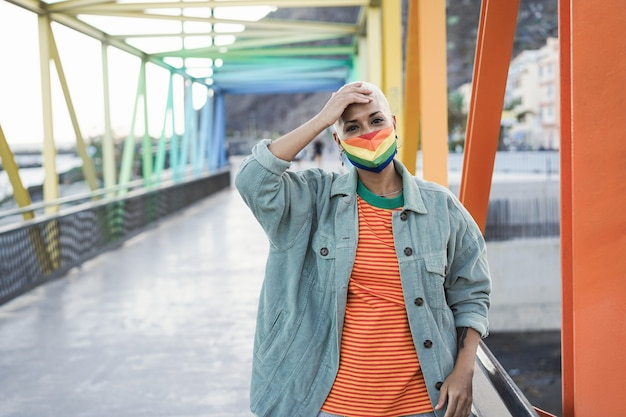 Jonge lesbienne die het trotse masker van de lgbt-regenboogvlag draagt - focus on face