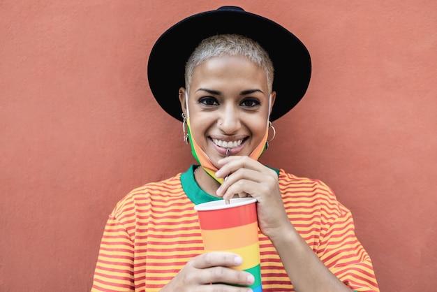 Jonge lesbienne die uit een regenboogvlagglas drinkt tijdens lgbt-trotsevenement
