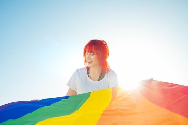 Jonge lesbienne kijkt neer met de gay pride parade op de voorgrond