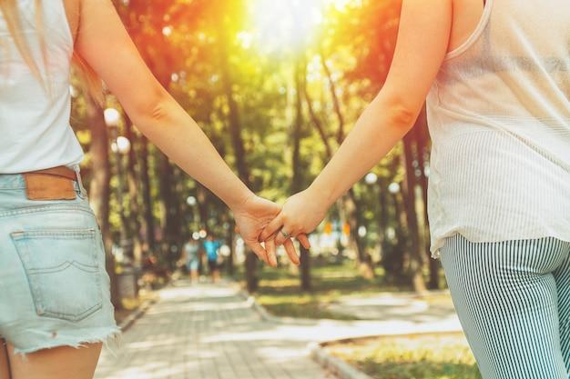 Jonge lesbische lgbt-paarholdingshanden die in het park lopen