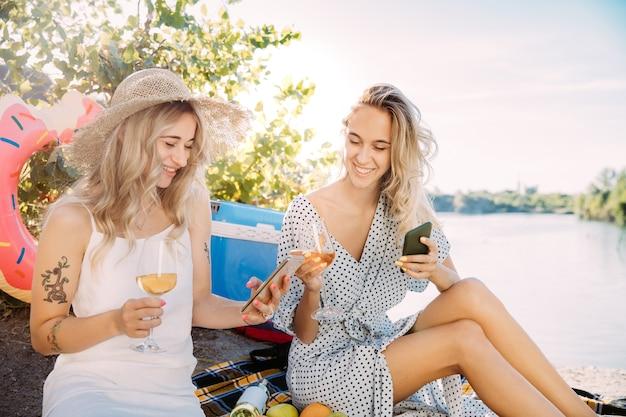 Jonge lesbische paar plezier op de rivier in zonnige dag. vrouwen besteden samen tijd aan de natuur. wijn drinken, selfie maken. concept van relatie, liefde, zomer, weekend, huwelijksreis.