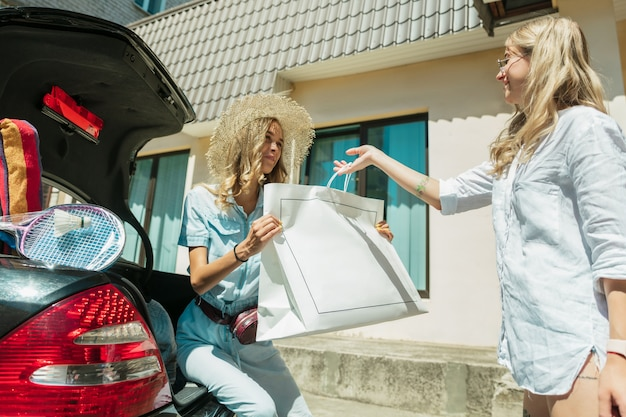 Jonge lesbische paar vakantie reis op de auto in zonnige dag voorbereiden. glimlachende en gelukkige meisjes voordat ze naar zee of oceaan gaan. concept van relatie, liefde, zomer, weekend, huwelijksreis, vakantie.
