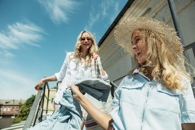Jonge lesbische paar vakantie reis op de auto in zonnige dag voorbereiden. lachende en gelukkige meisjes voordat ze naar zee of oceaan gaan. concept van relatie, liefde, zomer, weekend, huwelijksreis, vakantie.