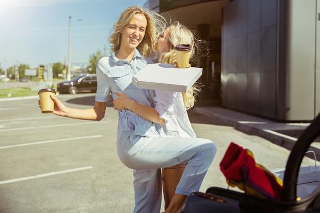 Jonge lesbische paar vakantie reis op de auto in zonnige dag voorbereiden