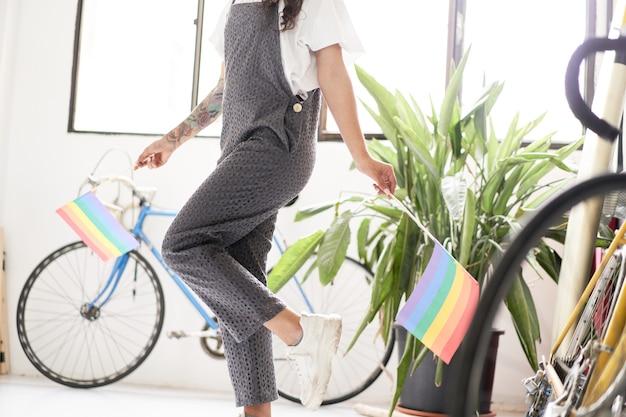 Jonge lesbische vrouw danst thuis met de lgbt-vlag en viert trots met vreugde alleen thuis