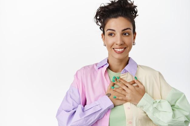 Jonge lesbische vrouw die hand op het hart houdt, gelukkig glimlacht en wegkijkt naar logo, wordt verheven, trots en lgbtq-concept op wit geïsoleerd