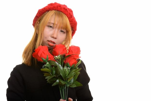 Jonge leuke aziatische vrouw die rode rozen houdt die droevig kijken