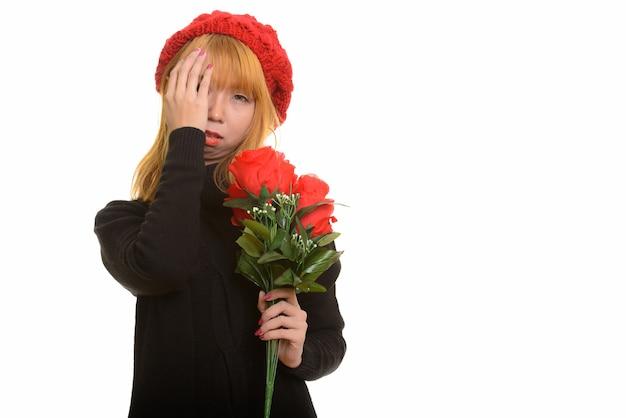 Jonge leuke aziatische vrouw die rode rozen houdt die gestrest kijken