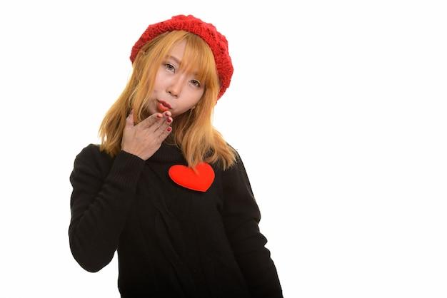 Jonge leuke aziatische vrouw met rood hart op borst en blazende kus