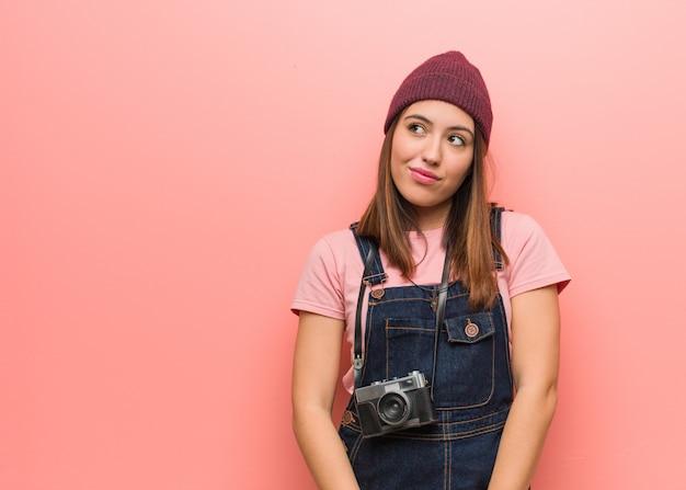 Jonge leuke fotograafvrouw die droomt van het bereiken van doelen en doeleinden