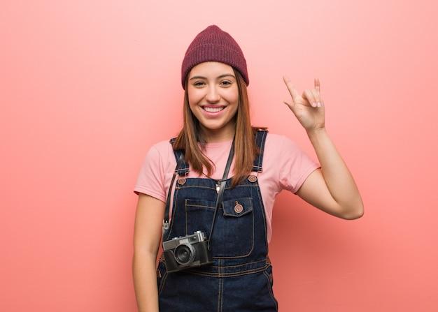 Jonge leuke fotograafvrouw die een rotsgebaar doet