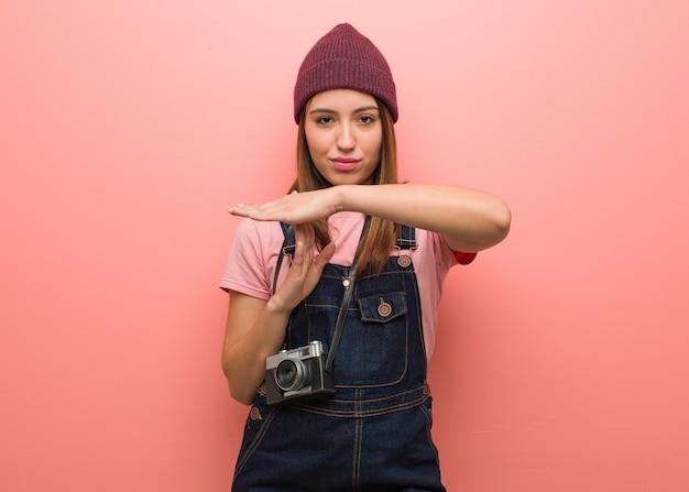 Jonge leuke fotograafvrouw die een time-outgebaar doet
