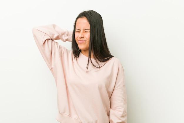 Jonge leuke spaanse tienervrouw die aan nekpijn lijden vanwege sedentaire levensstijl.