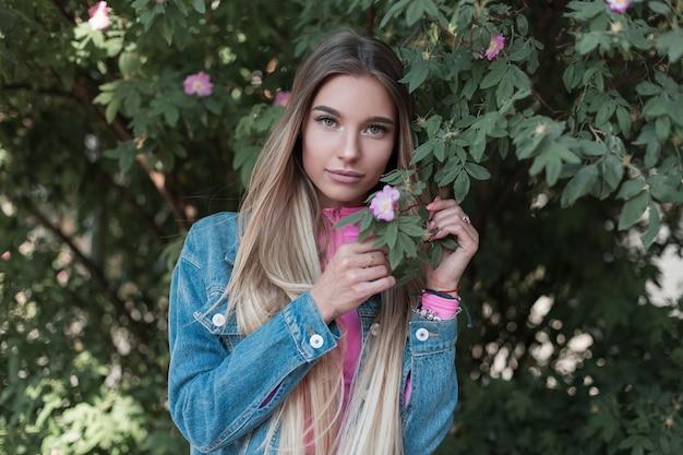 Jonge leuke vrolijke vrouw met lang haar in een modieus denim jasje in een trendy roze top in de buurt van een groene bloeiende struik in de straat. modern meisje model buiten rusten op een zomerdag. retro stijl.