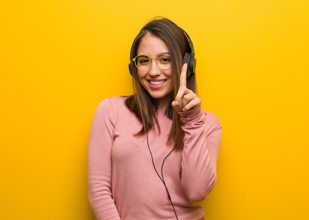 Jonge leuke vrouw die aan muziek luistert die nummer één toont