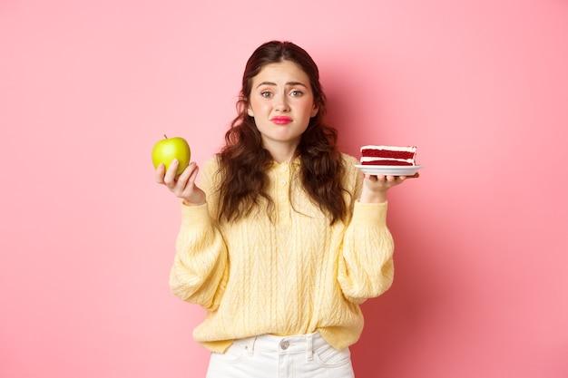 Jonge leuke vrouw die aarzelt tussen heerlijk fluitje van een cent dessert en groene gezonde appel, op dieet zijn, besluiteloos tegen roze muur staan.