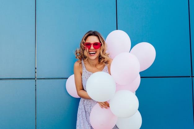 Jonge leuke vrouw die een bos van luchtballons houdt, die roze zonnebril draagt