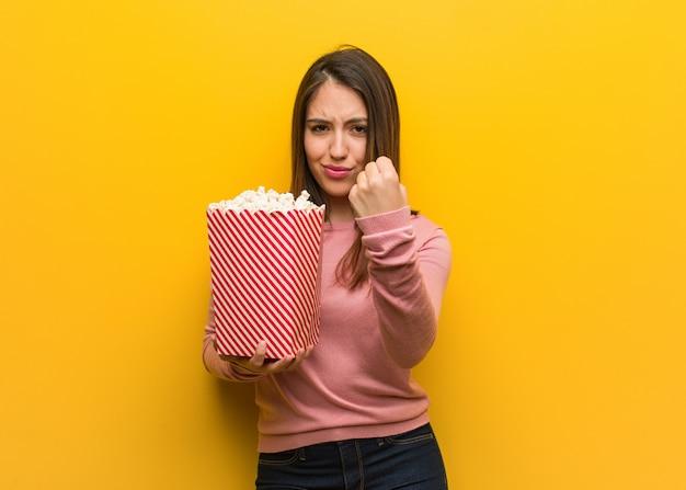 Jonge leuke vrouw die een popcornemmer houdt die vuist toont aan voorzijde, boze uitdrukking