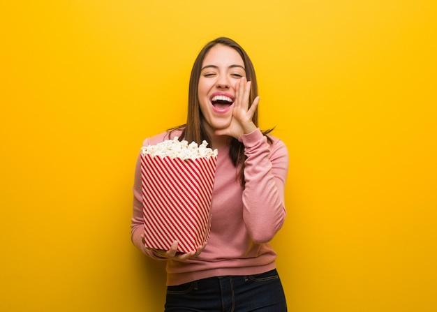 Jonge leuke vrouw die een popcornemmer houdt schreeuwend iets gelukkig aan de voorzijde