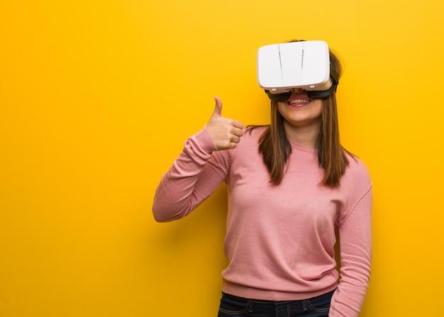 Jonge leuke vrouw die een virtuele werkelijkheid draagt googles die en duim omhoog opheft glimlacht