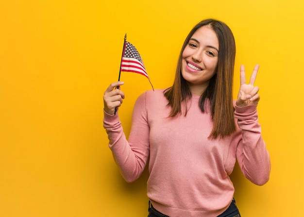 Jonge leuke vrouw die een vlag houdt die van verenigde staten nummer twee toont