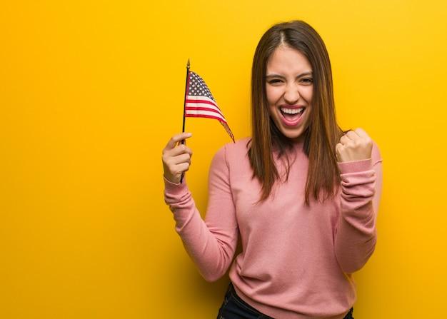 Jonge leuke vrouw die een vlag van verenigde staten verrast en geschokt houdt