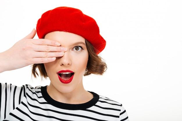 Jonge leuke vrouw die oog behandelt met hand.