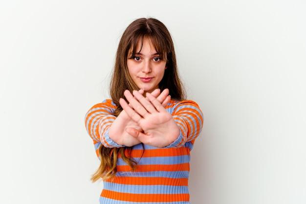 Jonge leuke vrouw die op witte muur wordt geïsoleerd die een ontkenningsgebaar doet