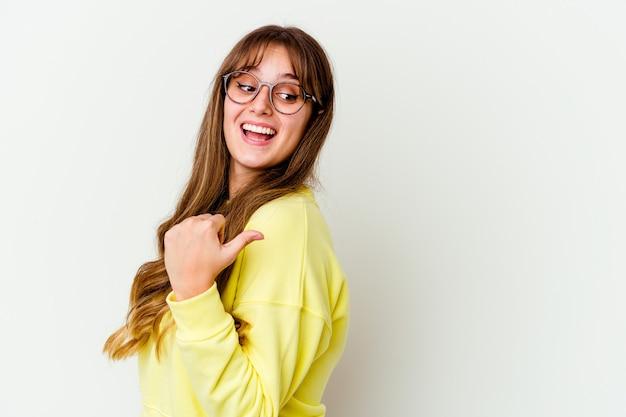 Jonge leuke vrouw die op witte muurpunten met weg duimvinger wordt geïsoleerd, lachend en zorgeloos