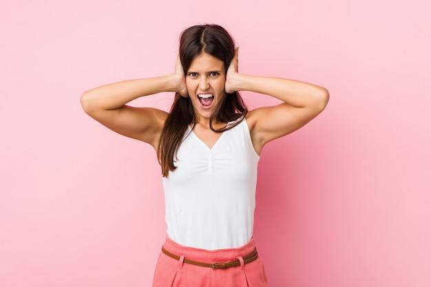 Jonge leuke vrouw die oren behandelen met handen die niet te hard geluid proberen te horen.