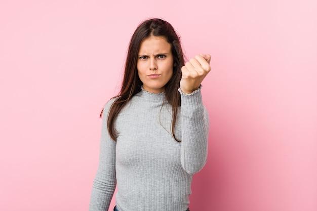 Jonge leuke vrouw die vuist toont aan camera, agressieve gelaatsuitdrukking.